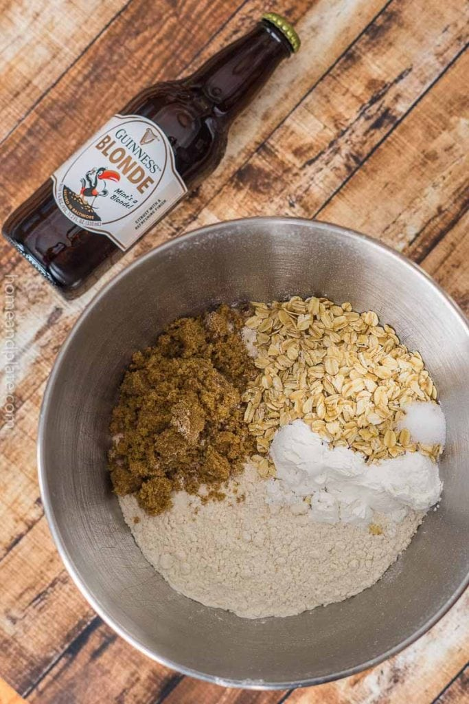 A bottle of beer on its side next to a bowl of flour, oats and brown sugar
