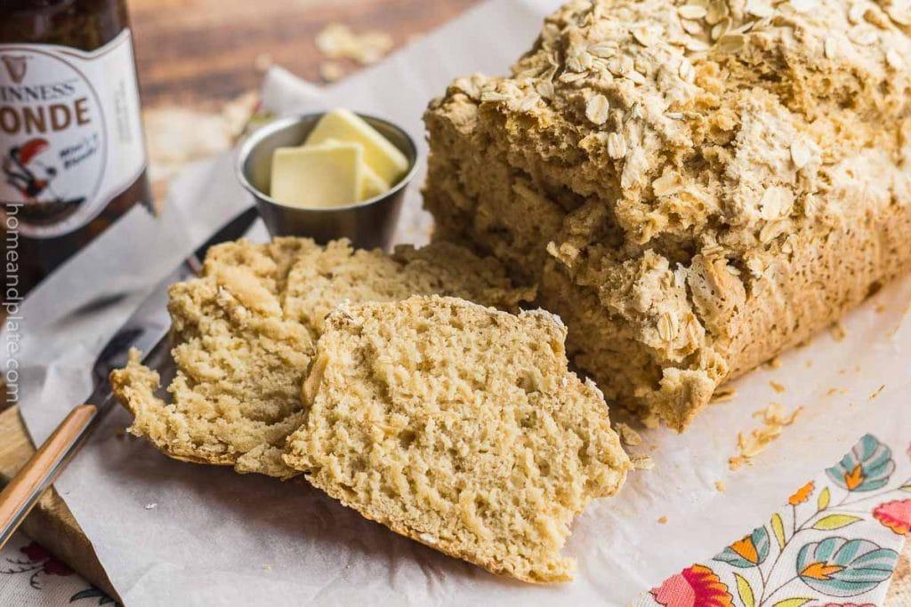 Side view of a loaf of bread on a wooden board beside a knife ramekin of butter