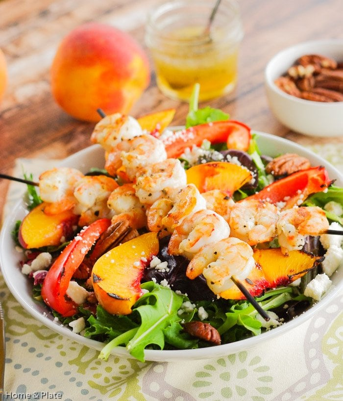Grilled Shrimp, Peach & Goat Cheese Salad with Honey Balsamic Vinaigrette | Home & Plate | www.homeandplate.com | This salad dotted with goat cheese and pecans and drizzled with a honey balsamic vinaigrette is a winner.