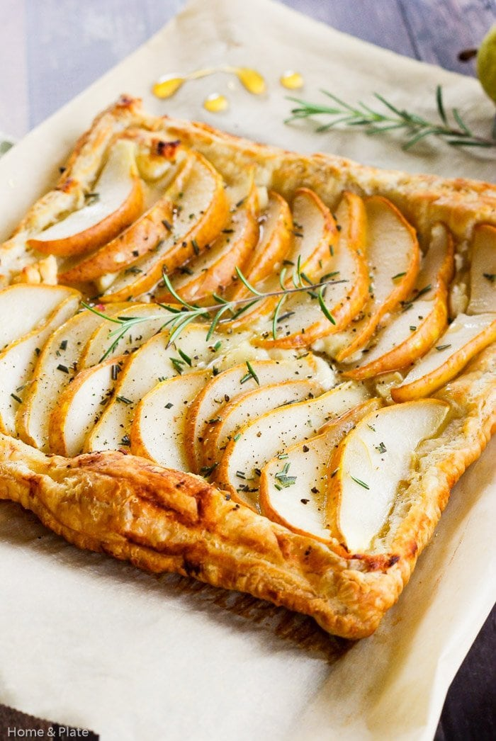 Closeup view of a Pear Tart with Goat Cheese, Rosemary & Honey on a baking sheet