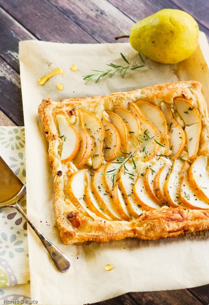 Front facing view of a Pear Tart with Goat Cheese, Rosemary & Honey on parchment paper