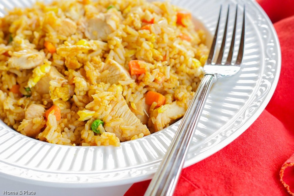 Side view of Better Than Takeout Chinese Fried Rice in white bowl with fork