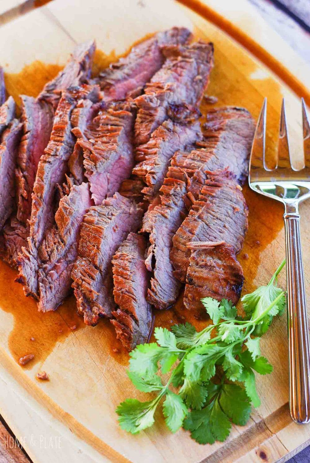 A board of thinly cut pieces of flank steak.