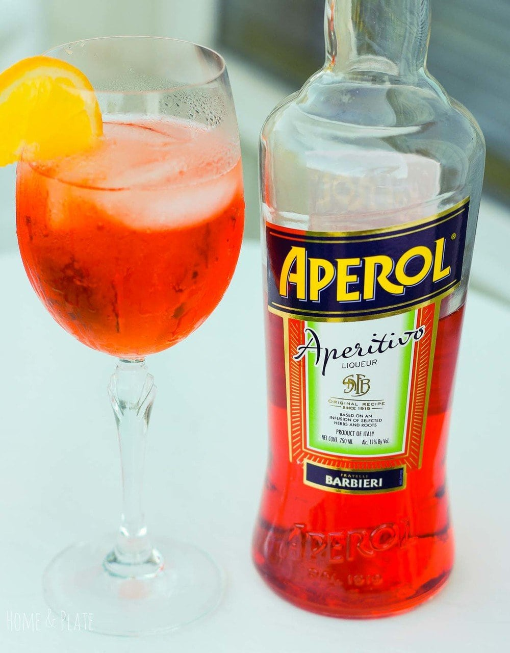 Front view of a bottle of Aperol with a glass of spritzer
