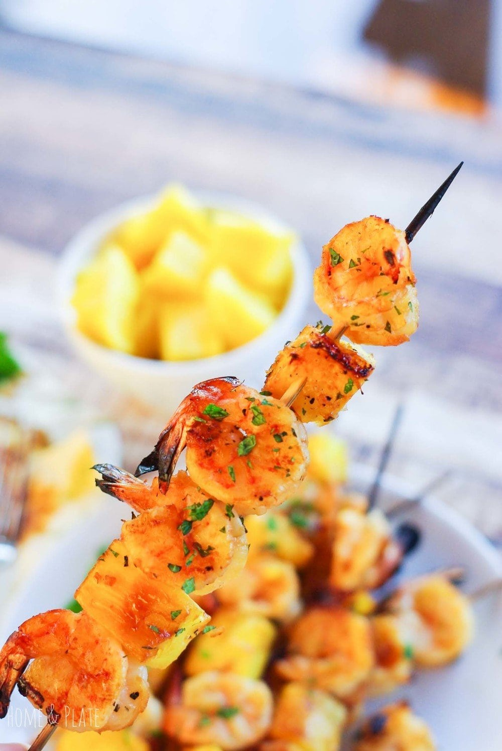 Close up view of shrimp and pineapple on a skewer