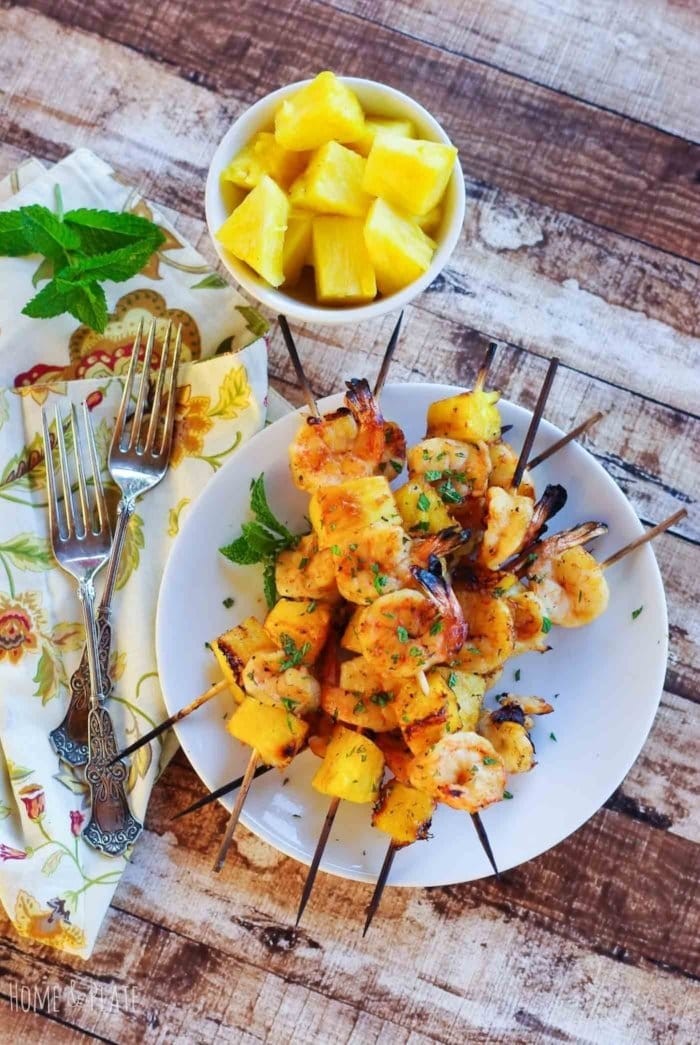 Overhead view of Shrimp Skewers on a white plate and a bowl of pineapple