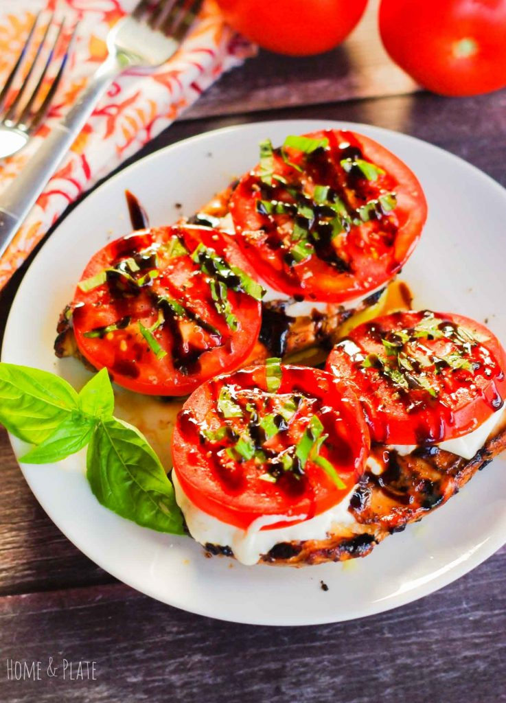 Platter of chicken topped with tomatoes and basil and drizzled with balsamic glaze