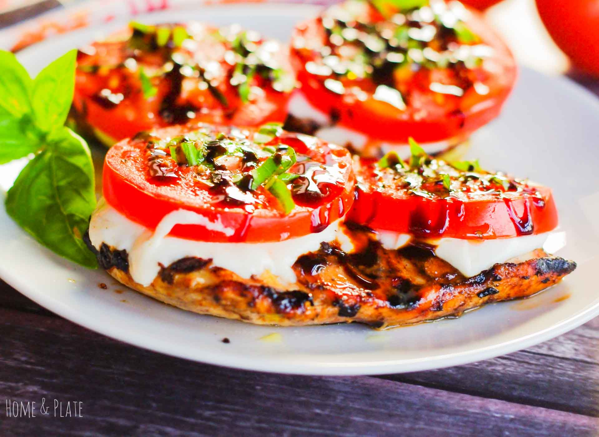 Balsamic Grilled Caprese Chicken | www.homeandplate.com | Fresh tomatoes, basil and mozzarella top these balsamic vinaigrette marinated chicken breasts. This delicious grilled chicken recipe is on the table in under 30 minutes.