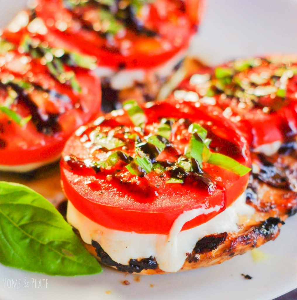 Tomato slice with basil on a piece of grilled chicken