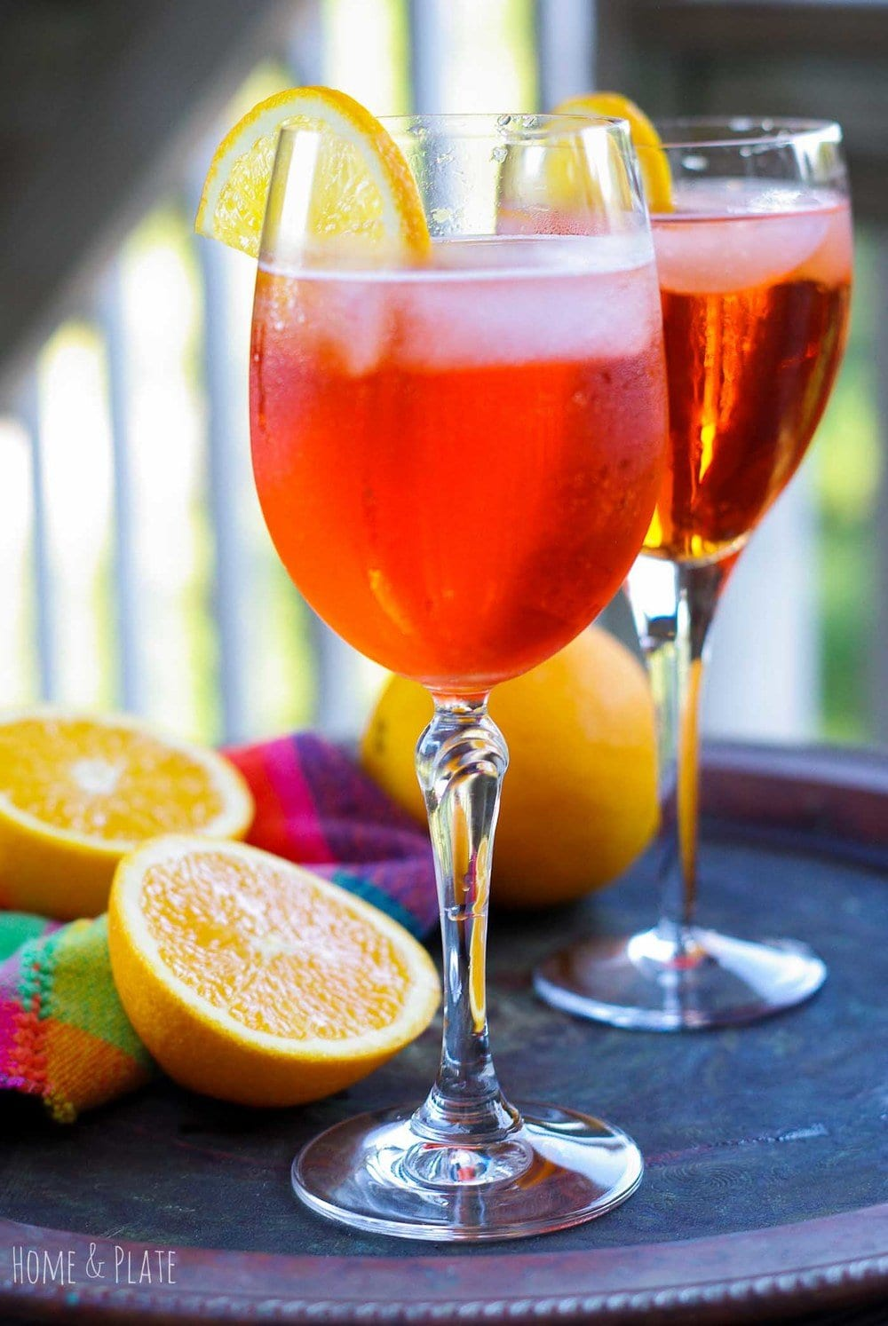 A glass of an Italian Aperol Spritzer on a platter surrounded by oranges.