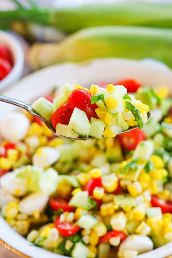 A spoonful of vegetables including tomatoes, corn and cucumber