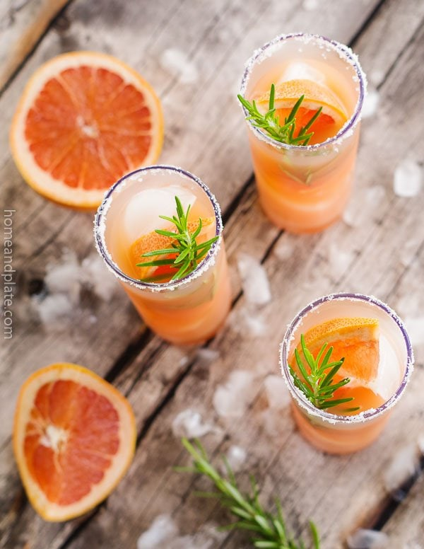 Overhead view of Grapefruit Salty Dog Cocktails surrounded by ice cubes, rosemary sprigs and grapefruit wedges