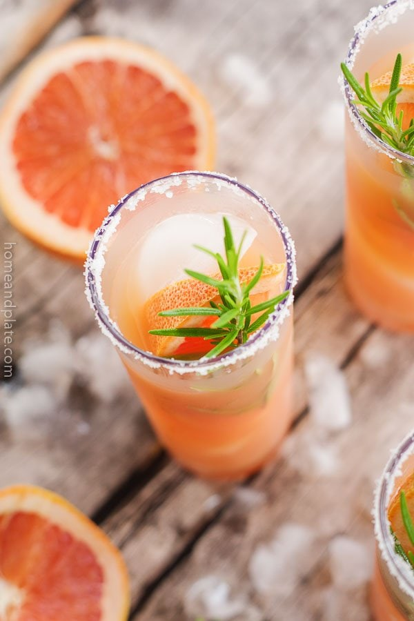 Close up shot of Grapefruit Salty Dog Cocktail surrounded by ice cubes and grapefruit wedges