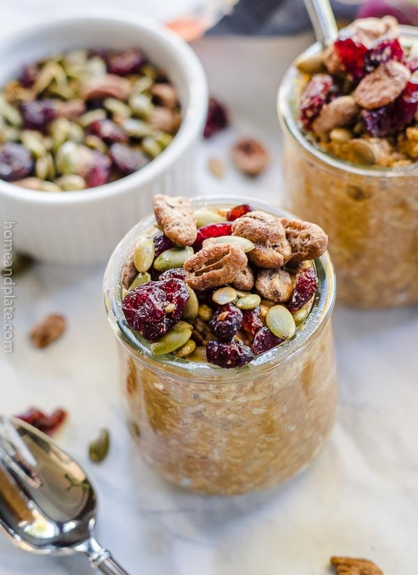 A close up of a small jar of overnnight oats sprinkled with dried fruit and nuts