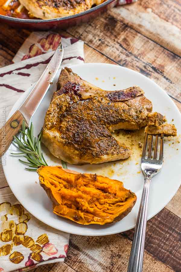 Pork chop on white plate with sweet potato