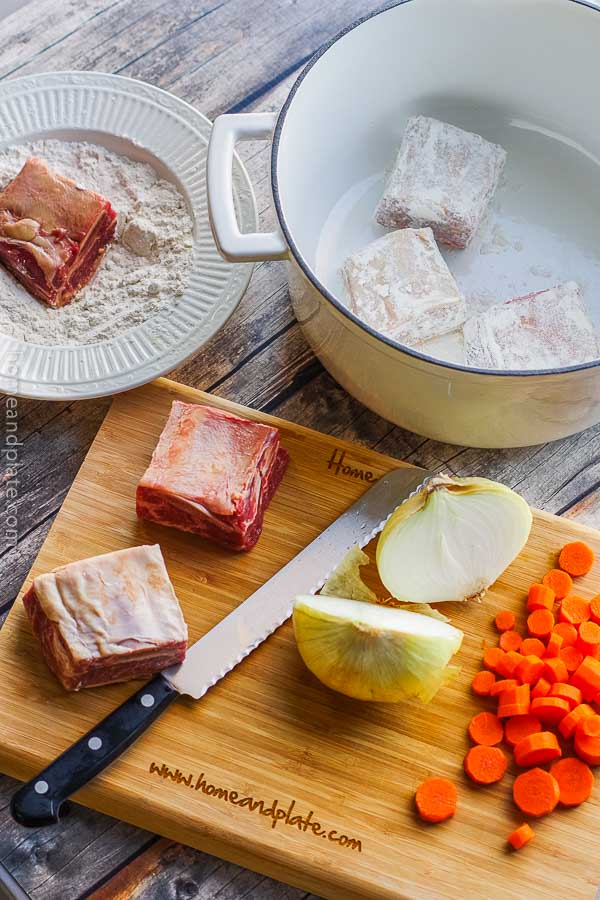 A recipe for Braised Beef Short Ribs | A cutting board with beef short ribs, onions and carrots next to a Dutch oven pot holding flour dredged beef short ribs.