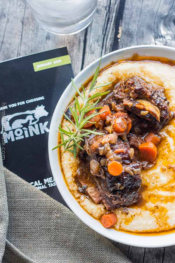 Braised Beef Short Ribs | Fall off the bone tender and delicious, these oven braised beef short ribs are cooked in a rich gravy and served on a bed of cheesy grits.