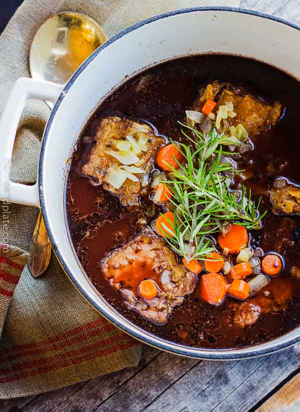 Braised Beef Short Ribs | Short ribs braising in a gravy of beef broth and red wine need a few hours in a Dutch oven.