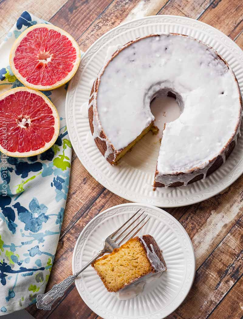 Overhead of glazed Grapefruit Pound Cake slice on white plate with whole cake next to it.