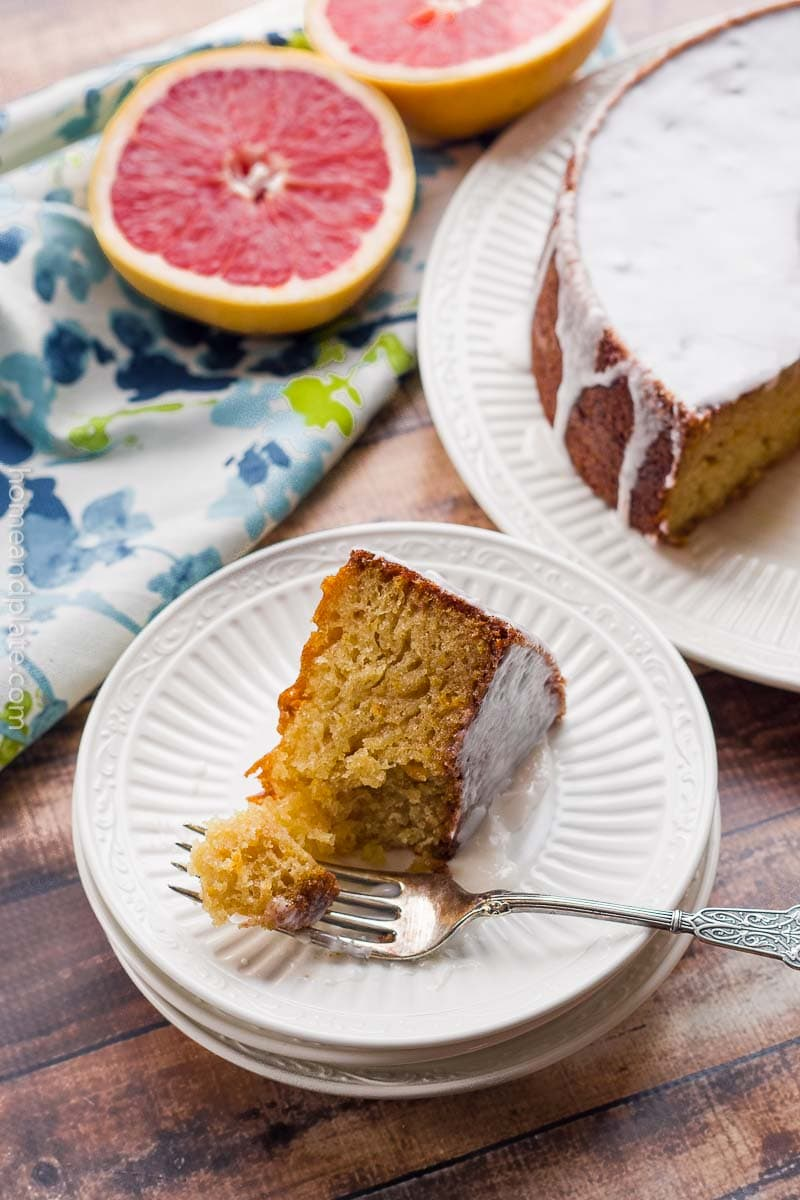 Sideview of glazed Grapefruit Pound Cake slice on white plate with whole cake in background