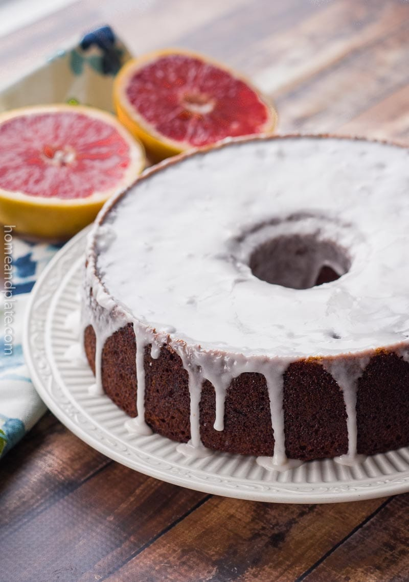 Sideview of glazed Grapefruit Pound Cake on white plate with sliced grapefruit in background