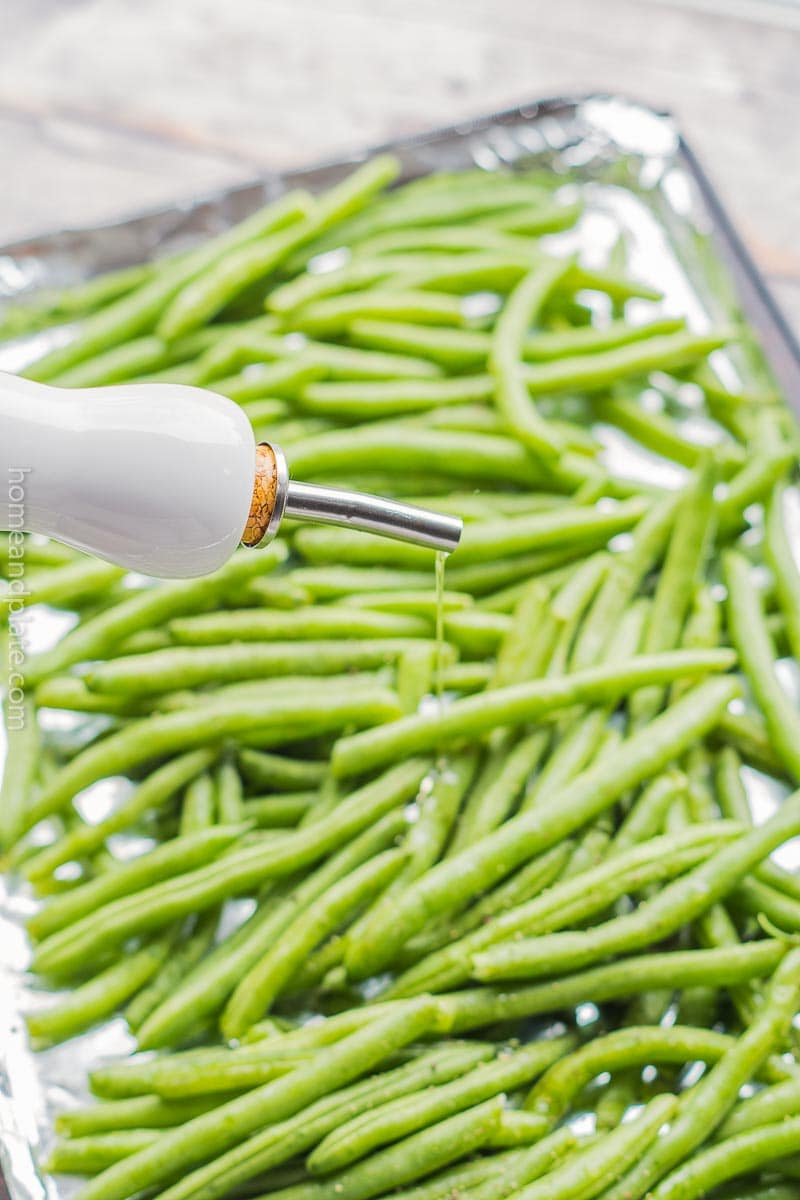 Olive oil being drizzled over green beans