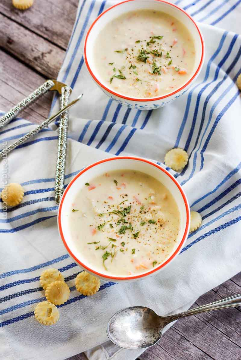 Two bowls of crab chowder on white and blue napkin