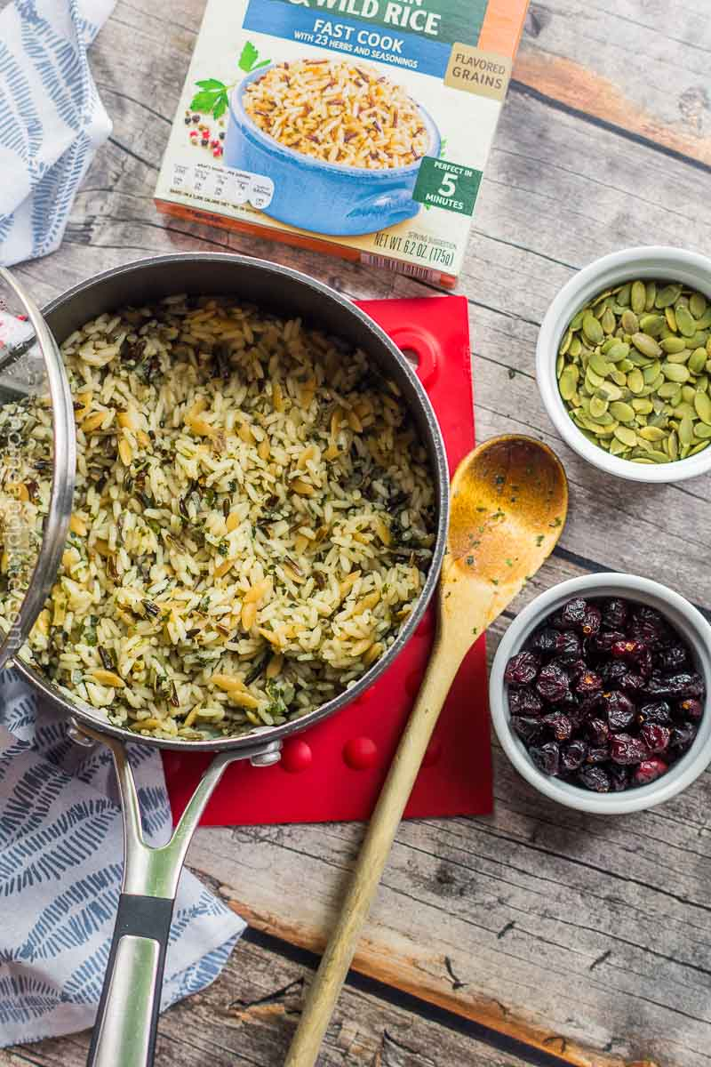 Pot of rice, dried cranberries and pepitas on wooden surface