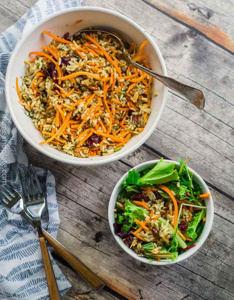 Large bowl of rice mixture next to smaller salad rice bowl