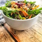 Bowl of wild rice salad on wooden surface