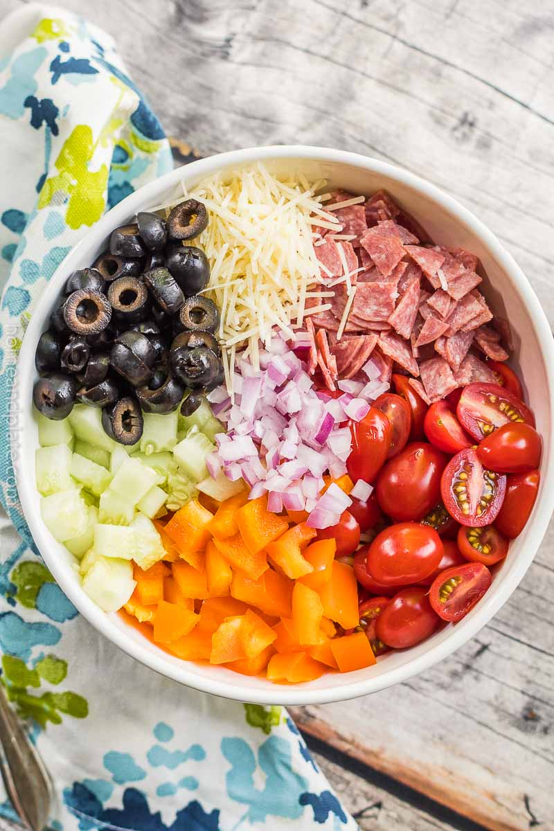 Tomatoes, salami, onion, peppers, cucumbers and black olives in a bowl.