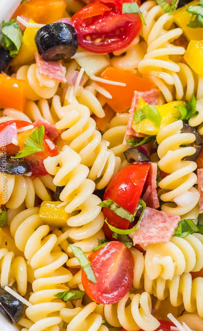 Close up of pasta noodles, tomatoes, salami and black olives.