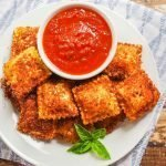 Overhead view of plate of fried ravioli with a cup of marinara