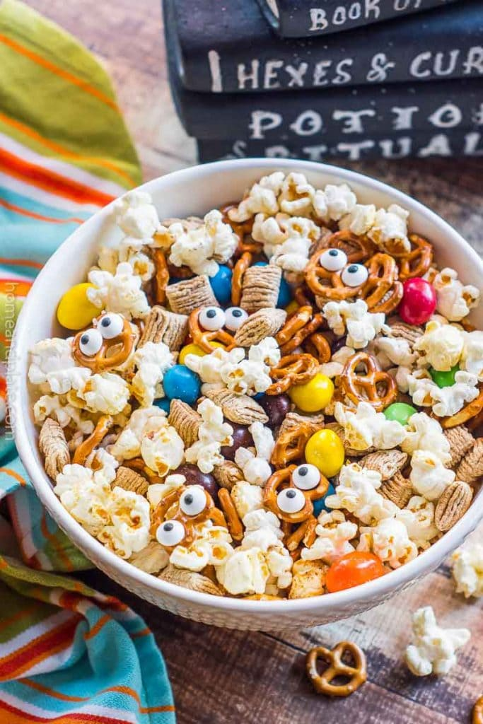 Bowl of Halloween snack mix next to stack of black books