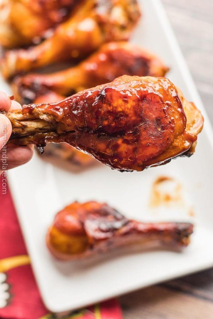 hand holding a baked honey chicken leg