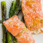 Two salmon filet on white plate with asparagus spears