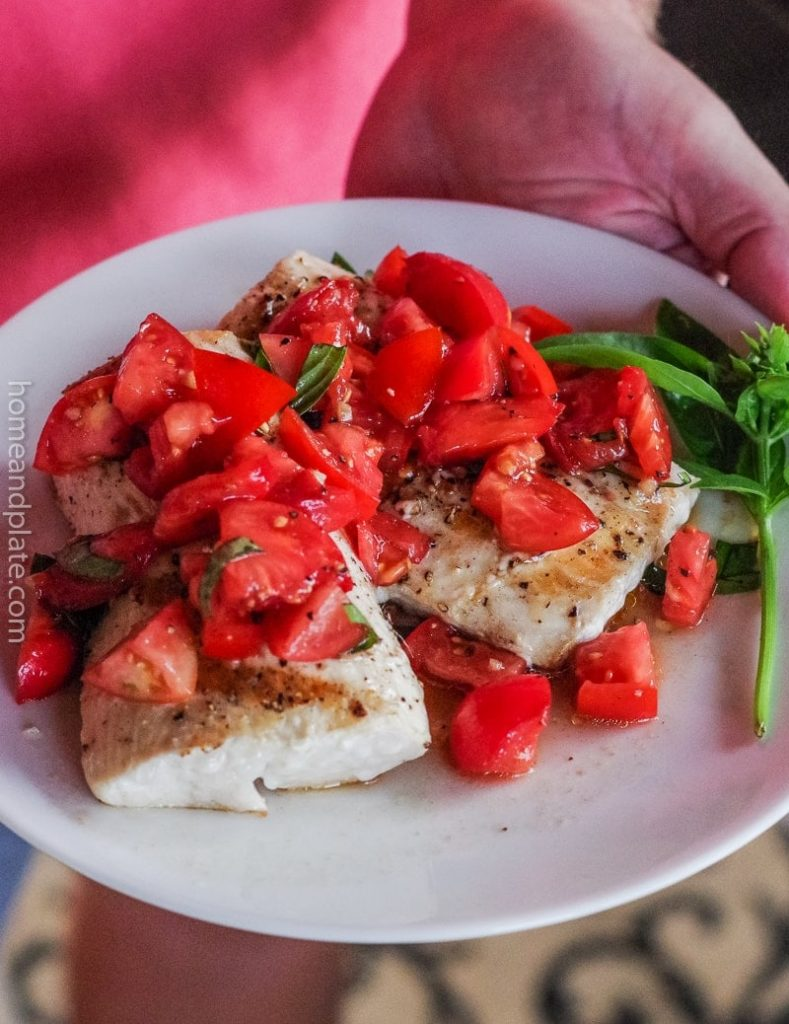 A person holding a dinner plate with grilled fish and tomatoes